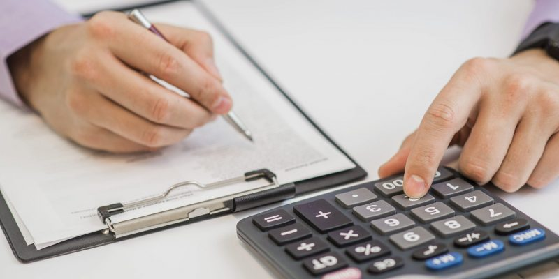 close-up-businessman-calculating-invoices-using-calculator-min